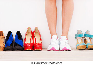 I made my choice! Cropped image of woman in sports shoes standing against the wall while high hilled shoes laying in a row near her
