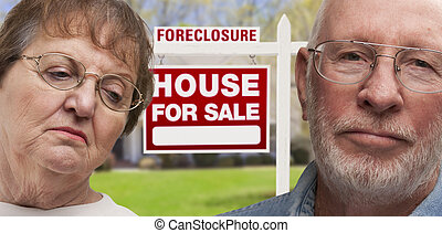 Depressed Senior Couple in Front of Foreclosure Sign and...