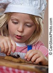 Cute young boy putting raisins on gingerbread
