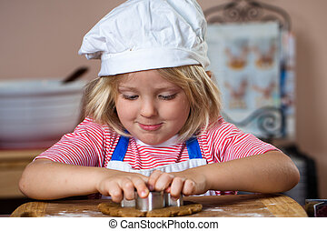 Cute boy making gingerbread man