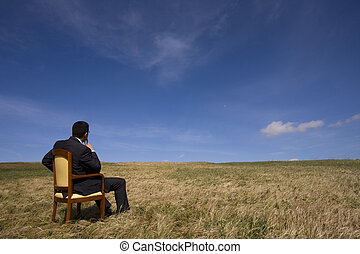Contemplation - businessman sitting in a chair in outdoor...