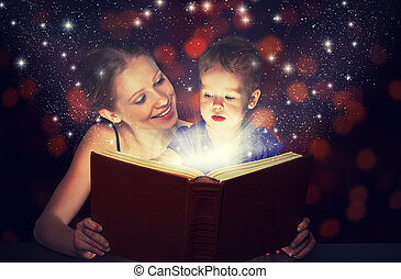 mother and child baby daughter reading magic book in dark -...