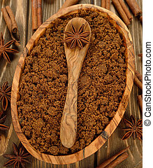 Brown sugar, anise and cinnamon on brown background closeup