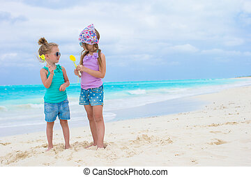 Little adorable girls with eggs on white tropical beach