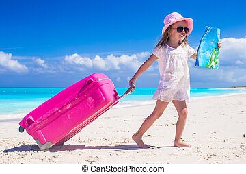 Little adorable girl with big colorful suitcase and a map in...