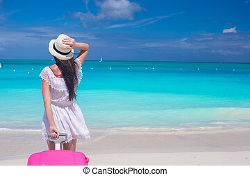 Young beautiful woman with large suitcase on tropical beach...