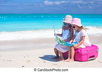 Little lovely girls sitting on big suitcase and a map at...