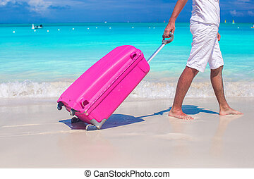 Close up a man pulls luggage on white sand - Close up a man...