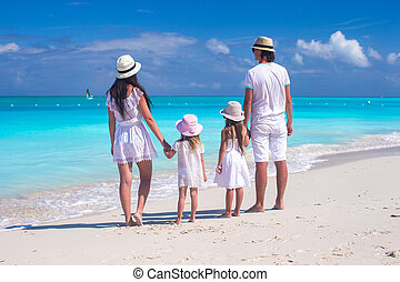 Back view of a young beautiful family on tropical beach -...