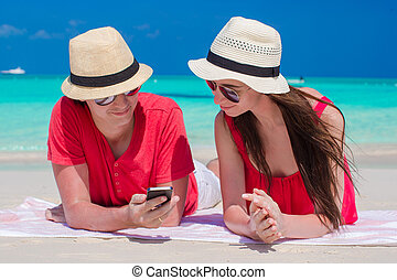 Young couple looking at phone lying on tropical beach