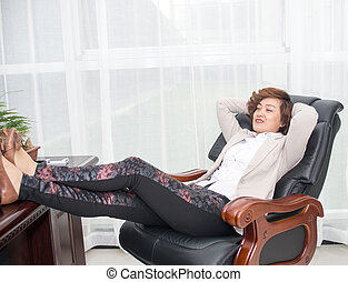 Relax female boss - Female business people lying on a chair...