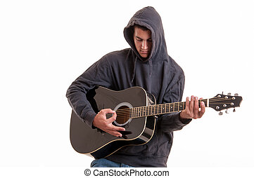 Pensive Teenager dressed in a hoodie, writing a song about life at acoustic guitar