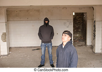 two street hooligans or rappers standing in a old abandoned...