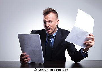business man reads his bills - young business man in shock...