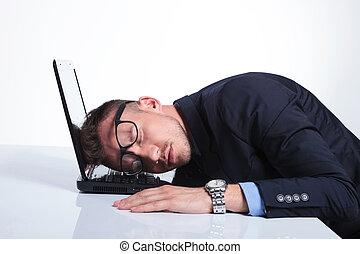 business man sleeps on laptop