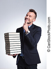 business man holds a pile of books