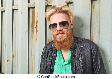 young bearded man smiles at you - portrait of a young casual...