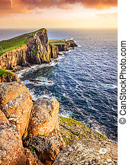 Vertical view of Neist Point lighthouse with rocks in foreground and rocky coastline, Scotland