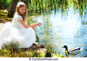 Cute girl in white dress feeding a duck.