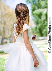 Girl in communion dress showing hairstyle. - Close up of...
