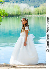Girl in communion dress at lake.