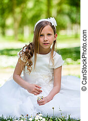 Girl in communion dress holding flowers.