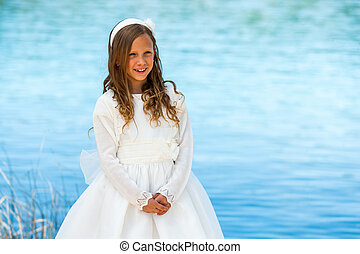 Sweet girl in white communion dress.