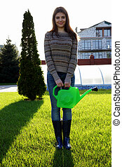 Cheerful woman standing with watering pot in garden