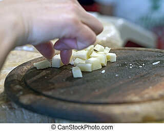 hand grasping cubes of cheese on a wooden cutting board - a...