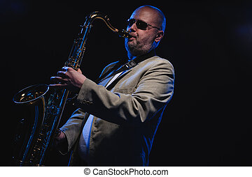 Saxophonist - Adult musician playing tenor saxophone, blue...