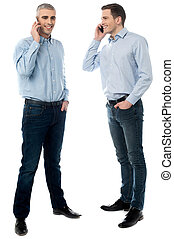 Two young men talking through mobile phone