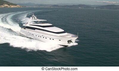 Aerial view of luxury yacht navigating close to the coast