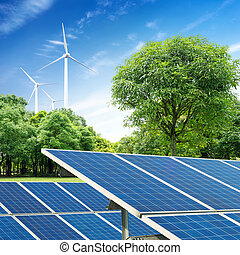 PV - Solar panels and wind turbine against blue sky
