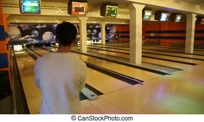 bowling - man rolls the ball and knocks down pins