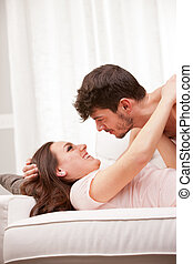 woman about to cuddle his man on a sofa in their living room...