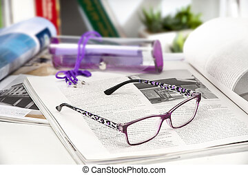 reading glasses endorsed on a magazine at home - modern...