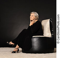 Smiling old woman sitting in black dress on dark background