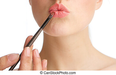 Young woman applying make up on lips - Half face portrait of...