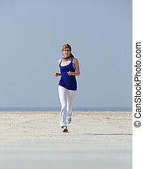 Middle aged woman jogging at the beach - Full length...