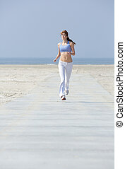 Woman jogging at the beach - Full body portrait of a middle...