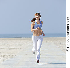 Fit active middle aged woman jogging - Full length portrait...