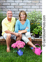 Senior couple gardening - Happy senior couple with flowers...