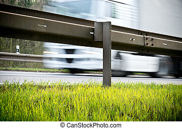 Guardrail - a crash barrier and roadside with going truck