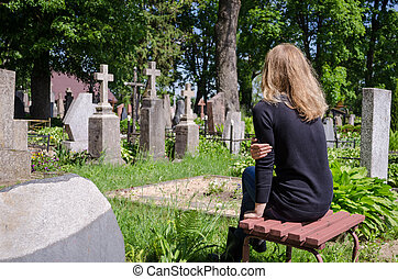 Sorrow woman near father husband tomb in cemetery - Sorrow...