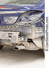 Car without a fender in repair shop.