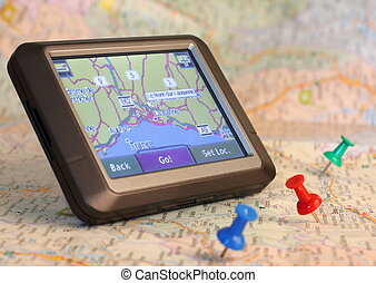 GPS device on traditional map, pins marking the travel route...