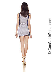 short dress - rear view of young pretty woman in a short...