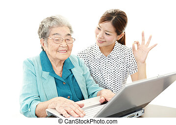 Old woman enjoys computer - Young woman helping an elderly...