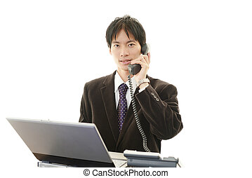 Smiling Asian businessman - Business man at laptop, shows...