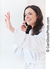 Hey darling! Beautiful young woman in bathrobe  talking on the mobile phone and smiling while looking through a window